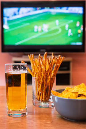 Watching football or soccer on television with beer, chips and breadsticks.