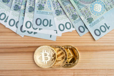 Gold physical Bitcoin, Litecoin and Ethereum coins with bunch of banknotes. Crypto currency vs traditional fiat money market.