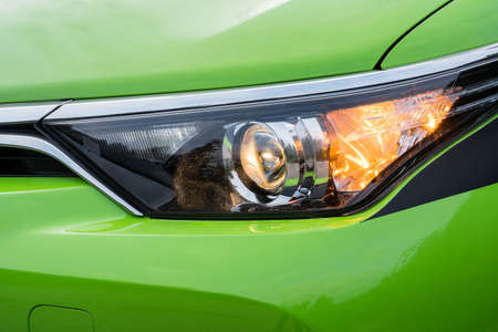 Front headlight on a modern green car. Low beam and turn signal or blinker