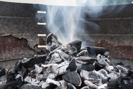 Black charcoal burning with smoke and fire in a barbecue grill. Delicious meal preparation.