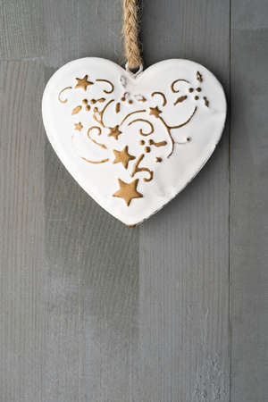 Festive heart shaped Christmas or New Year ornament with twine. Grey background. Vertical orientation. Copy space on the bottom.