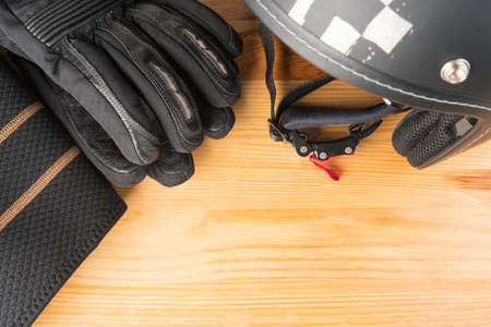 Motorcycle protective gear - helmet, gloves and kidney belt on a wooden background. Flat lay top view. Copy space on the bottom right corner. Stock fotó - 117531054