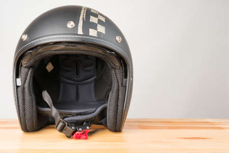 Motorcycle protective gear - open face helmet on a wooden background. Copy space on the right.