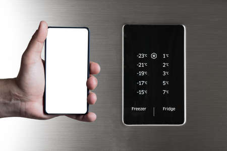 Hand holding frameless smartphone near fridge and freezer control panel. Internet of things abstract concept.