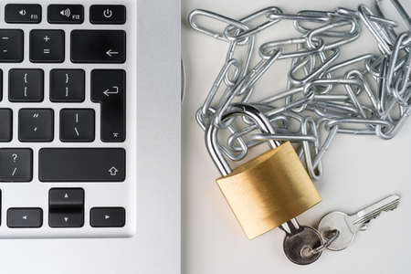 Padlock, chain and keys with laptop computer on a white background. Cyber security abstract concept.