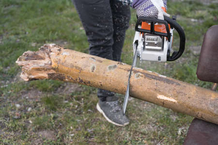 Man cutting wood with a chainsaw in a garden. Spring home improvment work. Winter fireplace preparation.