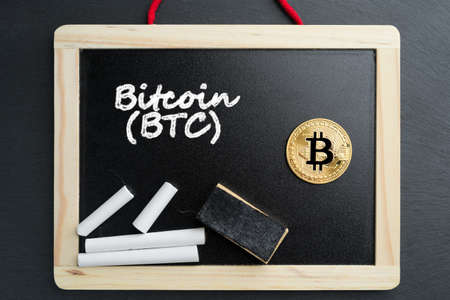 Physical Bitcoin gold coin on a blackboard with chalk text. Cryptocurrency education abstract concept. 版權商用圖片