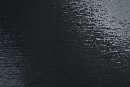 Dark black stone slate plate background.