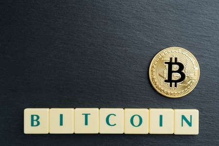 Physical Bitcoin gold coin with text made out of letter tiles. Cryptocurrency. Copy space in the top left corner. 写真素材