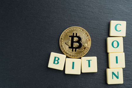Physical Bitcoin gold coin with text made out of letter tiles. Cryptocurrency. Copy space on the left.