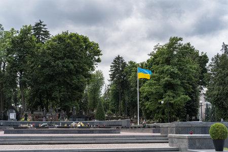 Lviv, Ukraine - July 2, 2019: Ukrainian flag fluttering on a Lychakiv Cemetery in Lviv, Ukraine.