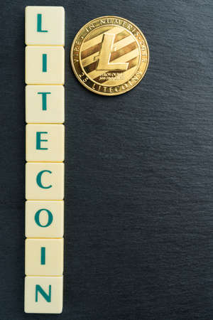 Physical Litecoin gold coin with text made out of letter tiles. Cryptocurrency. Vertical orientation. Copy space on the right. 免版税图像