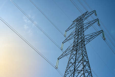 Overhead electrical power lines on a transmission tower against blue sky background. Electric energy distribution concept.