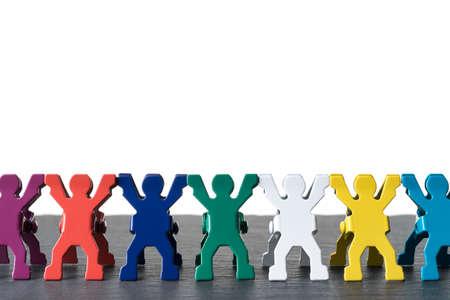 Bunte verschiedene Miniatur-Menschenfiguren, die in einer Reihe auf einer dunklen Steinschieferplatte stehen. Isoliert auf weißem Hintergrund. Vielfalt abstraktes Konzept. Standard-Bild