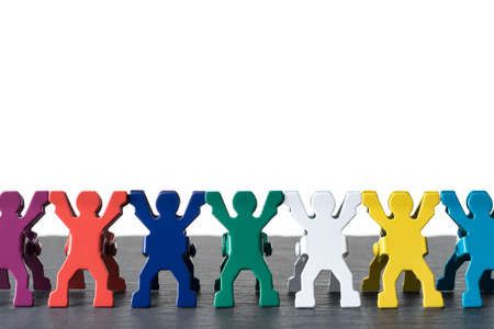 Colorful diverse miniature people figurines standing in a row on a dark stone slate plate. Isolated on white background. Diversity abstract concept. 写真素材