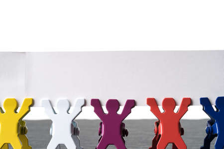 Colorful diverse miniature people figurines standing in a row on a dark stone slate plate. Blank banner with copy space. Isolated on white background. Diversity abstract concept. 写真素材