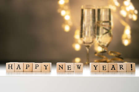 Happy New Year text made out of wooden blocks. Two glasses of champane with festive new year's eve decoration in the background. Copy space in the top left corner. Stock fotó