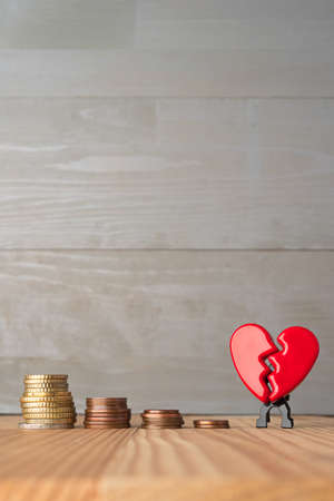 Broken red Valentine's Day heart with descending stacks of euro coins. Love and money problems abstract concept. Vertical orientation. Foto de archivo - 135391551