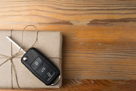 Car key on a box wrapped in paper with twine bow on natural wooden table background. Christmas or Valentine's Day gift or present abstract concept. Copy space on the right. Flat lay top view.