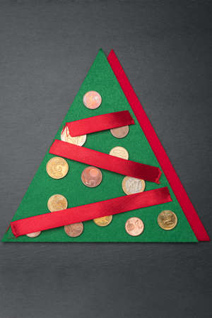 Green and red Christmas tree shape with baubles made out of Euro coins with ribbon chain or garland on dark black slate plate background. Vertical orientation. Flat lay top view.