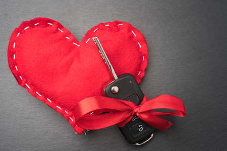 Car key with red bow and a heart on dark black slate plate background. Christmas or Valentine's Day gift or present abstract concept. Reklamní fotografie