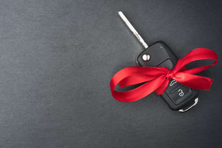 Car key with red bow on dark black slate plate background. Christmas or Valentine's Day gift or present abstract concept. Copy space on the left. Flat lay top view. Reklamní fotografie