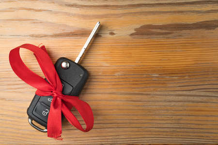 Car key with red bow on natural wooden table background. Christmas or Valentine's Day gift or present abstract concept. Copy space on the right. Flat lay top view.