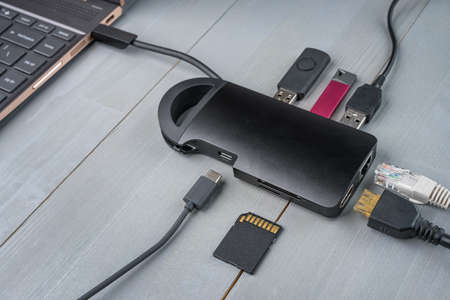 USB Type C adapter or hub connected to the laptop with various accessories - pendrives, hdmi, memory card, cables.