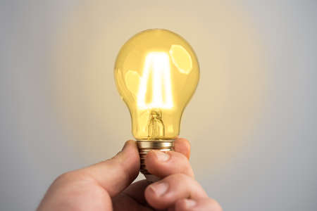 Caucasian man holding glowing incandescent light bulb. Idea or thought abstract concept.