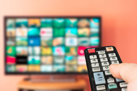 Caucasian man choosing what to watch on TV at home. Video on demand or VOD abstract concept. Changing channels and adjusting volume with television remote control. Standard-Bild