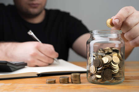 Coins in a jar, stacks of change and young caucasian man dropping money and writing in a notebook. Tax forms, counting savings, money collecting or accounting abstract concept.