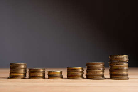 Stacks of coins on a natural wood background. Finance market growth abstract concept. Copy space at the top. Banco de Imagens