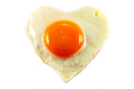 fried egg with heart shape on white background Horizontal photo