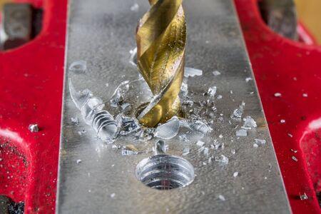 구멍을 뚫고 골드 컬러 드릴 비트의 마이크로 샷.