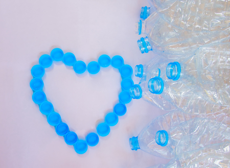 Empty plastic bottles of water for recycle with heart shape from bottle cap on white background Stock Photo