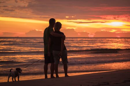 Happy couple hugging on the beach in colorful sunset with dog Stock Photo