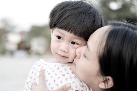 Closeup young mother kissing her son Banco de Imagens