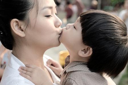 mujer hijos: Primer madre e hijo besando juntos