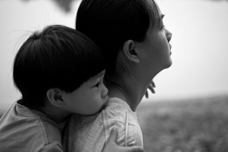 comforted: Young boy on back of his mother : Soft focus Stock Photo