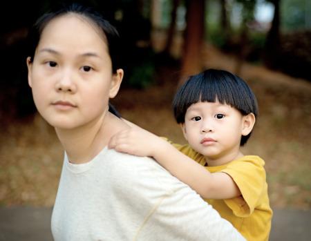 mamá hijo: Muchacho joven Primer en la espalda de su madre Foto de archivo