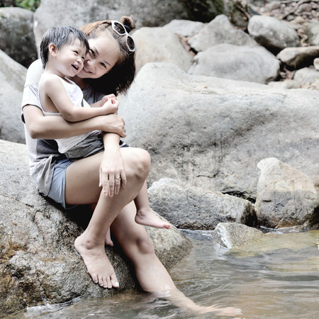 ittle: Happy ittle boy and young mother sitting on the rock at river