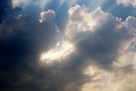 light rays: Light rays shine through the dark clouds