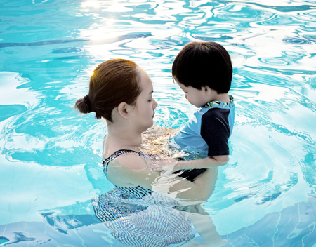 young boy in pool: Mother hugging her son  in the swimming pool at sunset : Soft focus Stock Photo