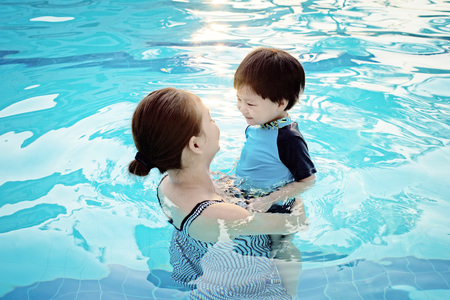 Mother and her son having fun in the swimming pool at sunset : Soft Focus Imagens