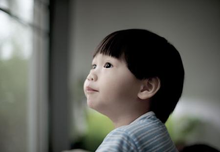 through window: Closeup little boy looking through window