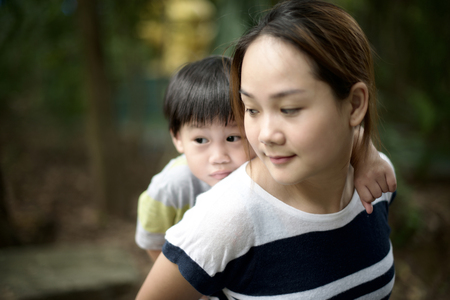 comforted: Closeup young mother giving piggyback ride to her son : Out of focus Stock Photo
