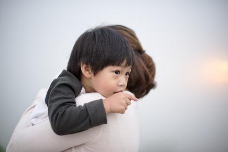 어린 소년 포옹 어머니는 자신의 손가락을 가리키는