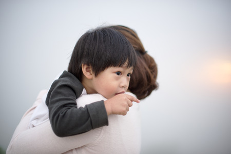 Mother hugging a little boy points his finger Imagens