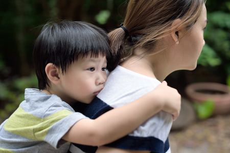 comforted: Young boy on back of his mother : out of focus