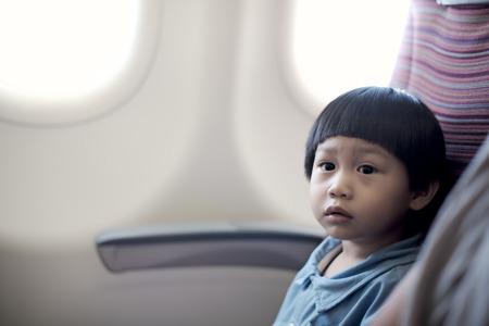 El pequeño niño se sienta en el plano: Primer